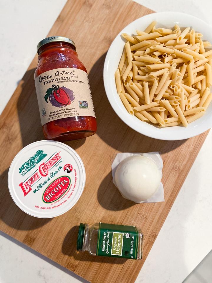 Marinara sauce, pasta, and ricotta on a wooden board