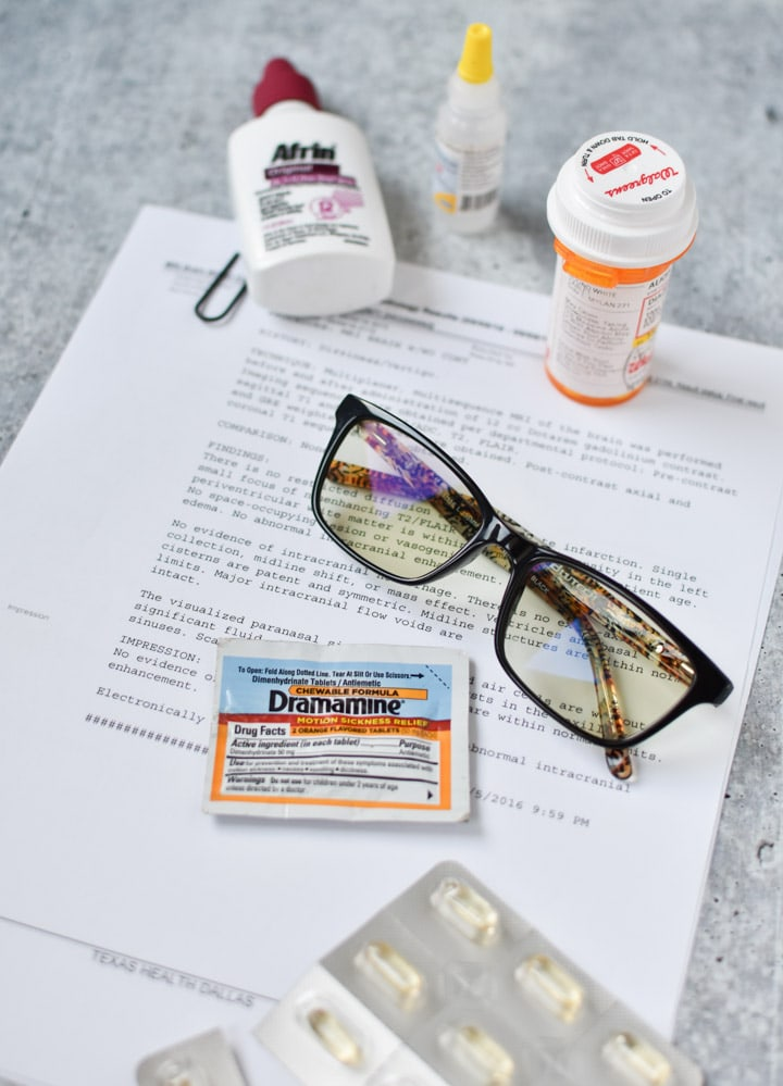 Pills, migraine glasses, afrin and eye drops scattered on a table