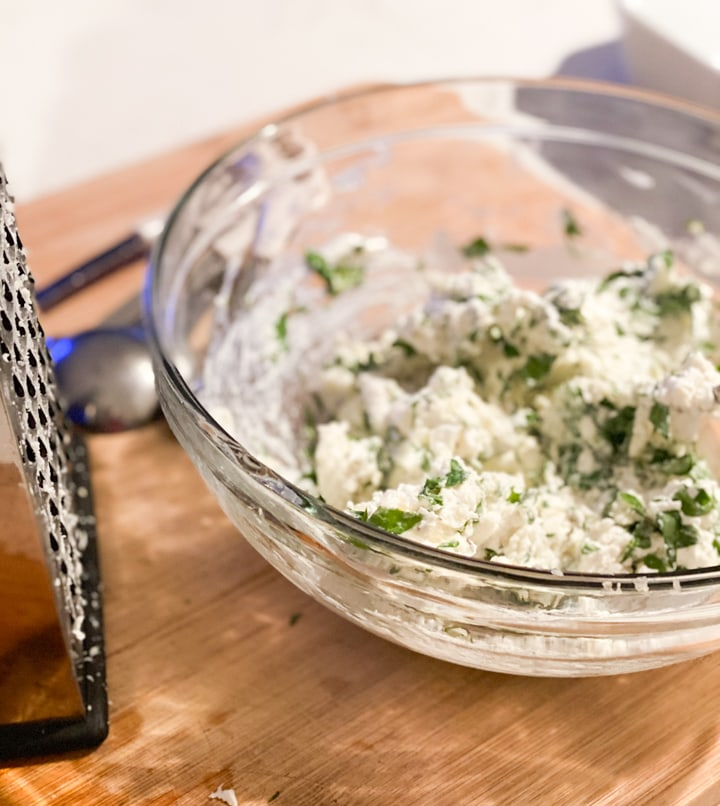 Mixture of ricotta and herbs in a bowl with a cheese grater
