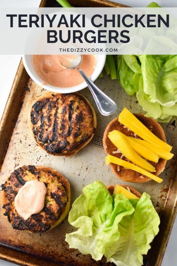 An open chicken burger with spicy mayo on a pan