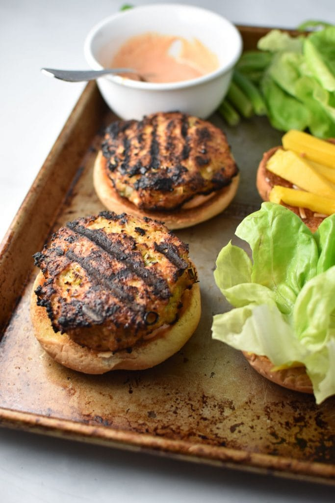 Two teriyaki chicken burgers next to buns with butter lettuce and mango, a container of spicy mayo in the back