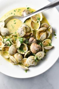 Clams in creamy sauce with parsley in a large white bowl