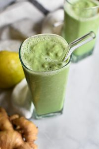 A green pear smoothie on a marble table with ginger and a whole pear