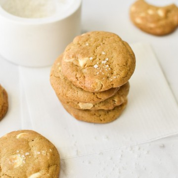 A stack of white chocolate chip cookies with sea salt on top