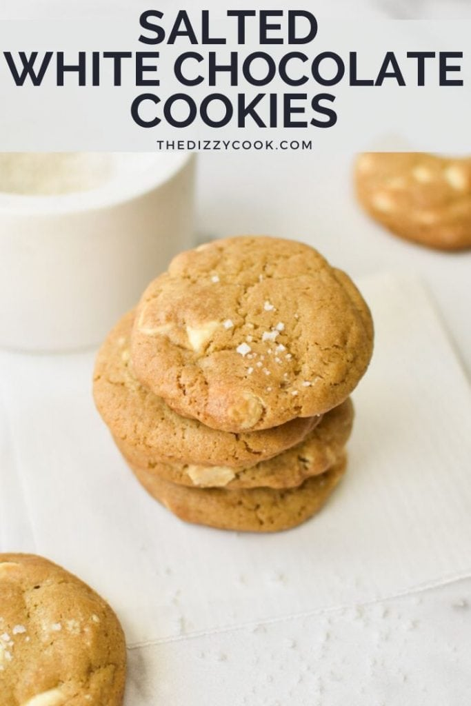 A stack of white chocolate chip cookies next to a bowl of sea salt