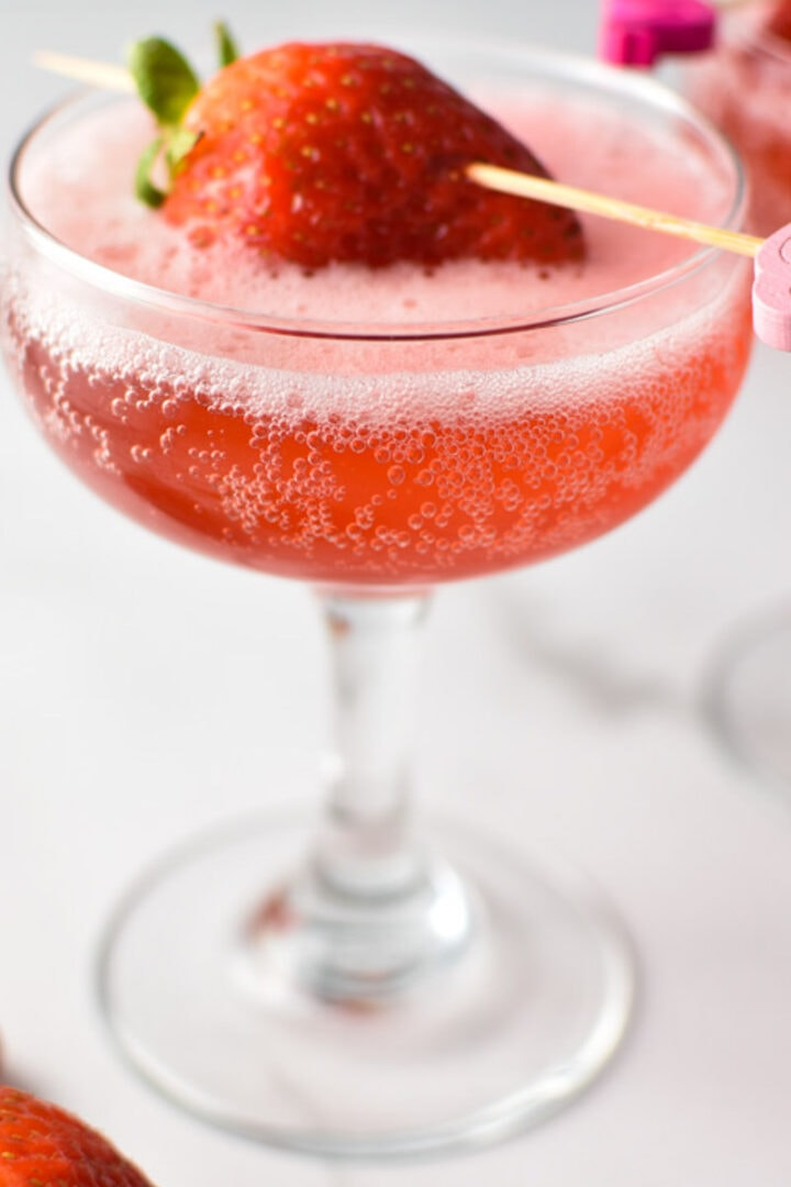 A pink strawberry mocktail spritzer in a coupe glass with a strawberry on the top