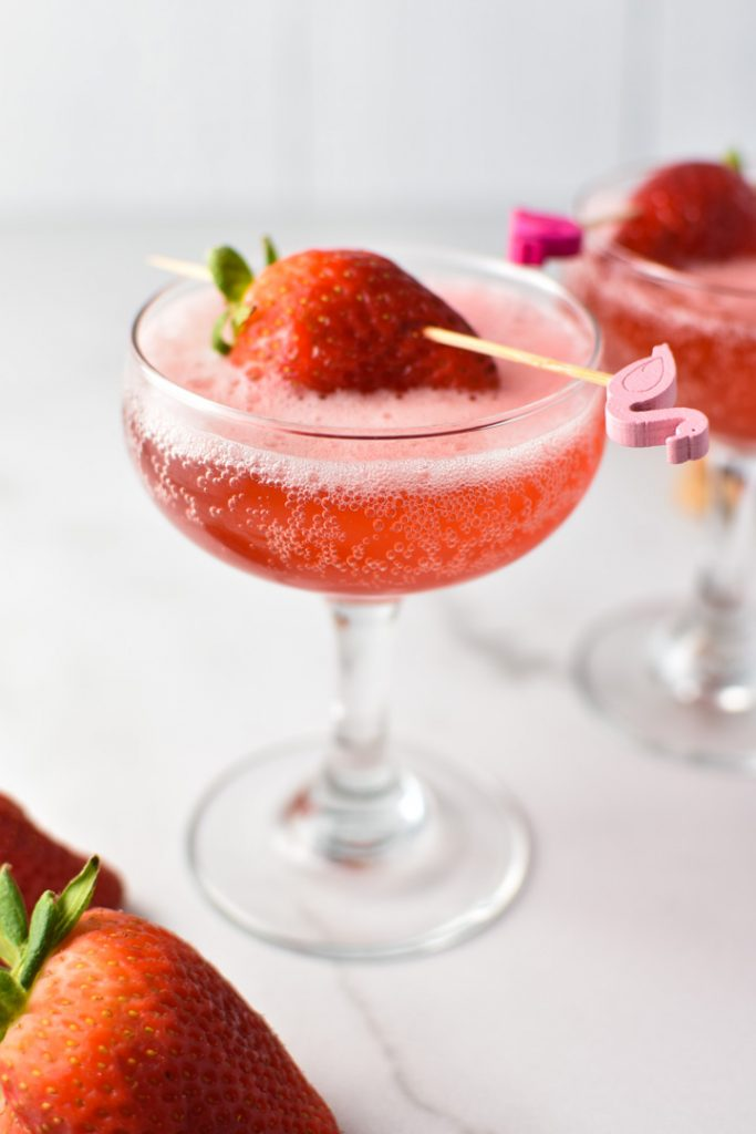 Two strawberry mocktails in coupe glasses with a strawberry on top