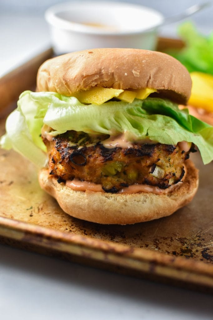 An assembled teriyaki chicken burger with butter lettuce, mango, and spicy mayo