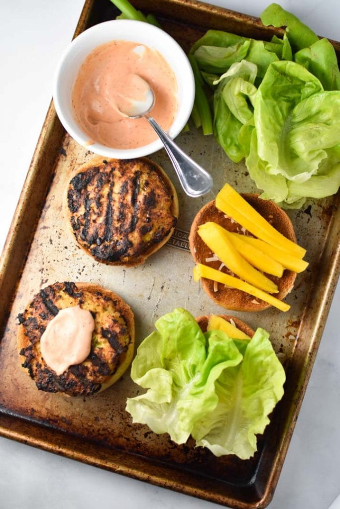 Two teriyaki chicken burgers, one with spicy mayo, on a sheet pan with toppings