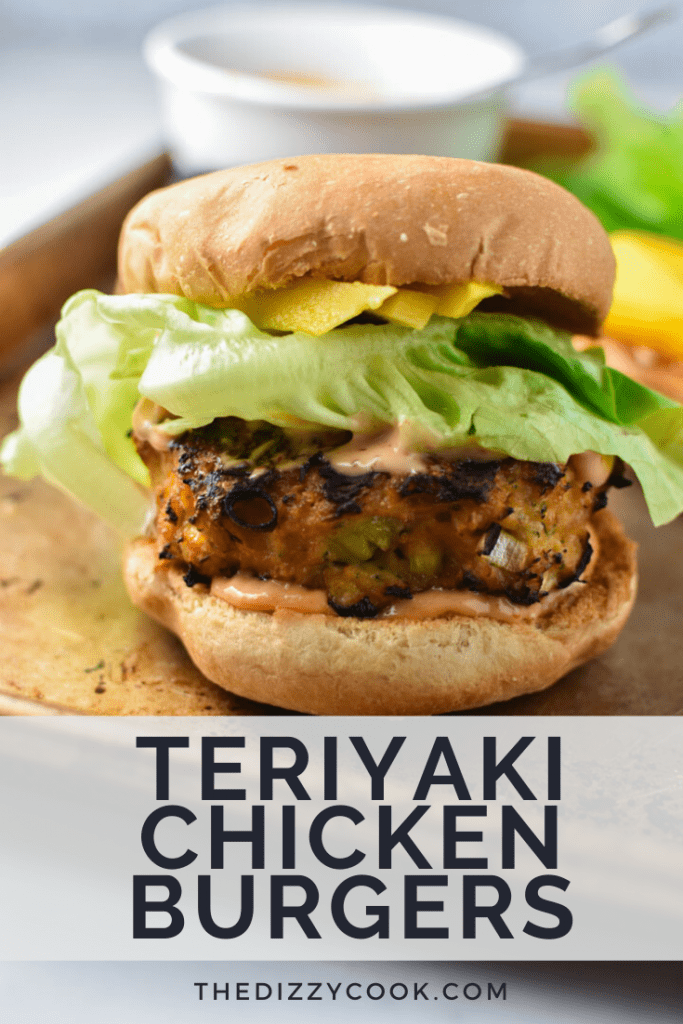 An assembled teriyaki chicken burger with spicy mayo, butter lettuce, and mango peaking out from under the bun