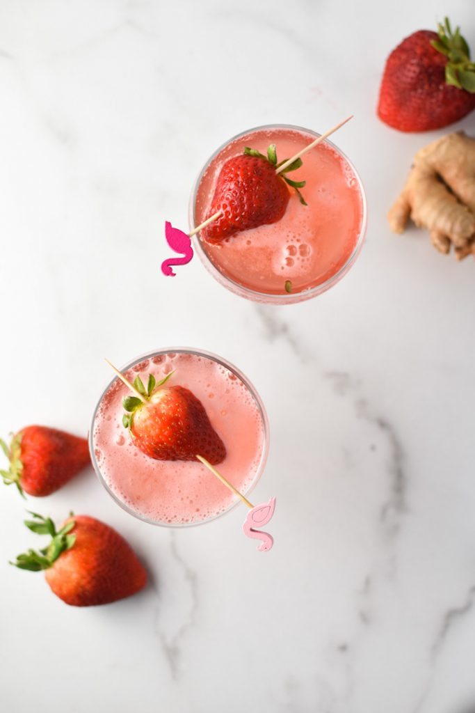 An overhead shot of two coupe glasses of strawberry simple syrup with strawberries and ginger surrounding it.