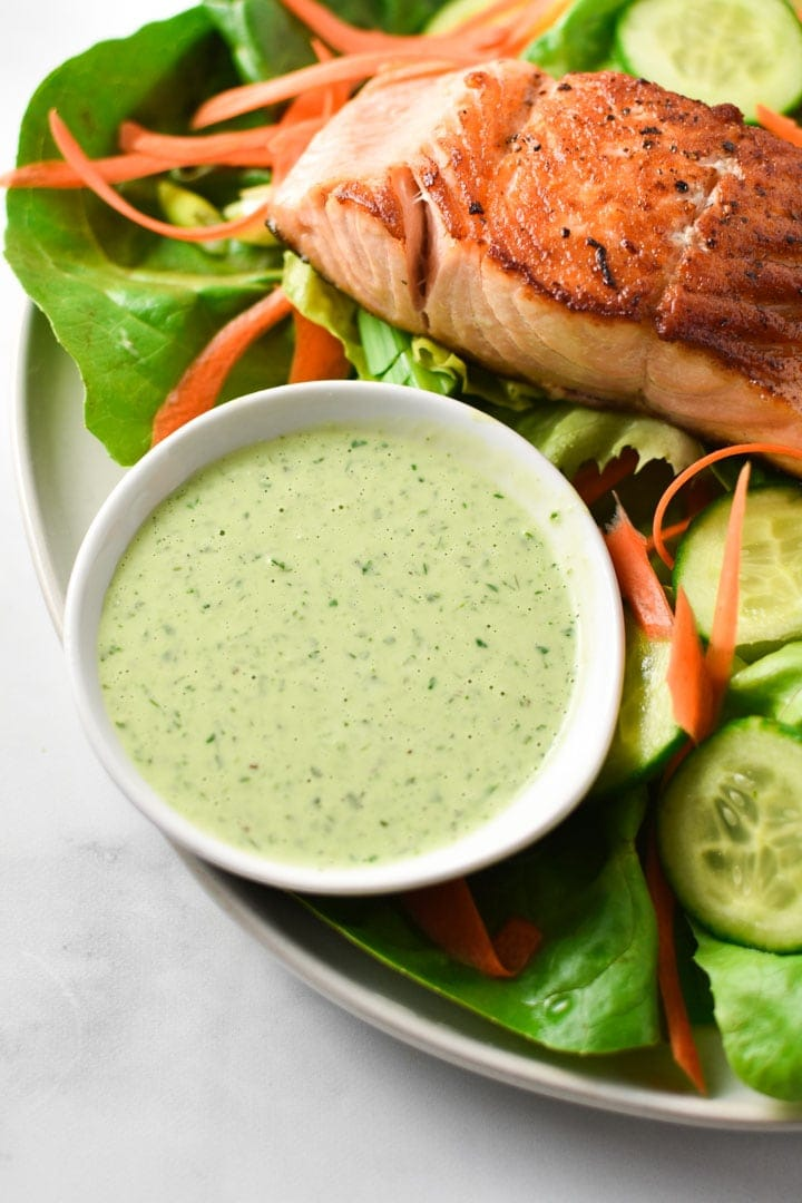 A bowl of creamy basil dressing next to seared salmon on a green salad