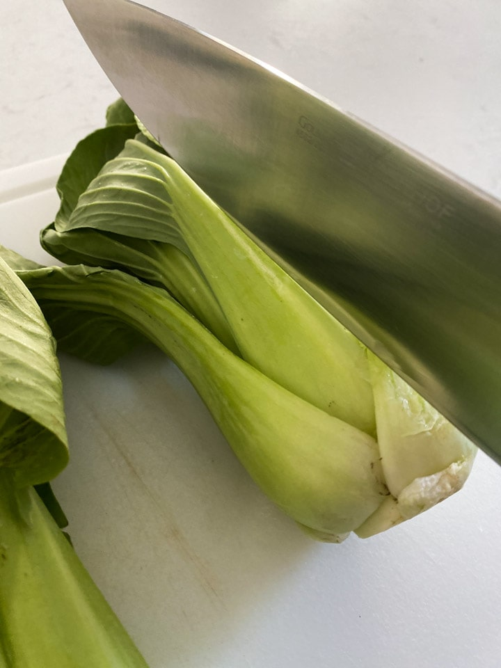 Sliced a bok choy in half with a knife on a cutting board