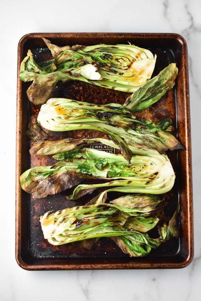 Four grilled baby bok choy halves on a metal sheet pan