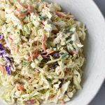 Healthy coleslaw topped with apples in a white bowl
