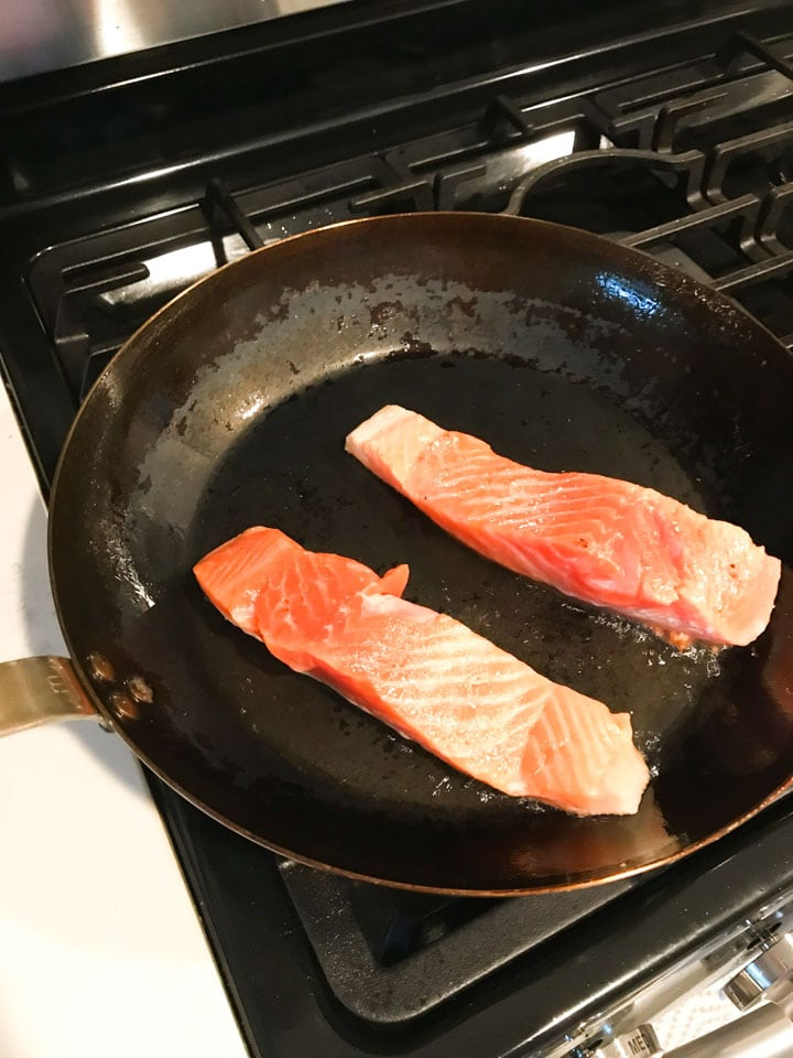 Two salmon filets being seared in a cast iron pan