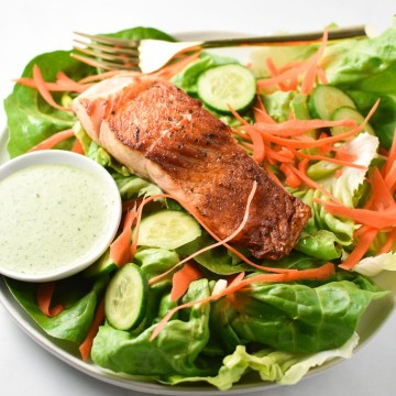 Pan seared salmon salad with creamy basil dressing on the side