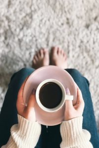 A woman holding a cup of black coffee