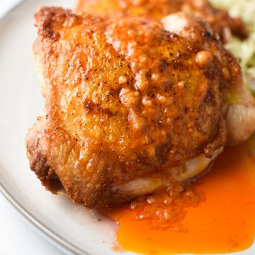 Buffalo chicken thighs dripping in sauce on a grey plate