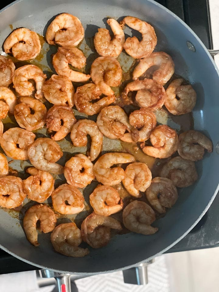 Shrimp covered in a spicy marinade being cooked in a large pan