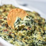 A round pita chip being dipped into a creamy spinach artichoke dip