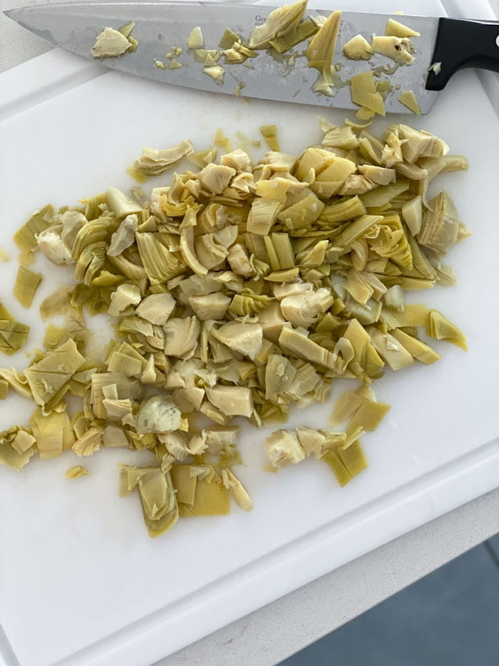 Artichoke hearts being chopped on a white cutting board