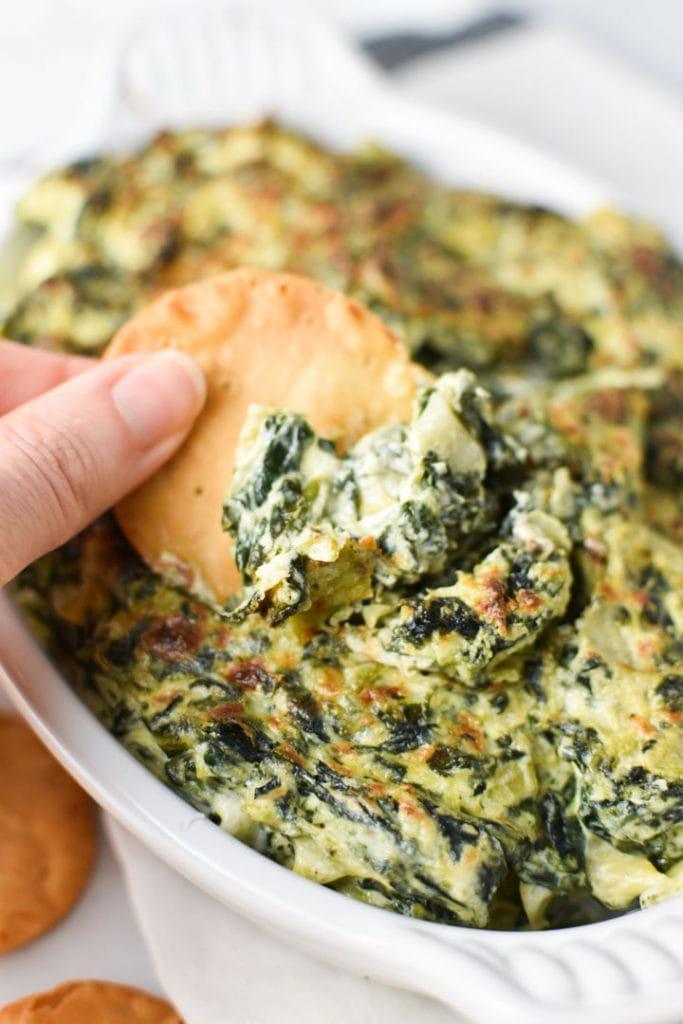 A hand dipping a pita chip into creamy spinach artichoke dip