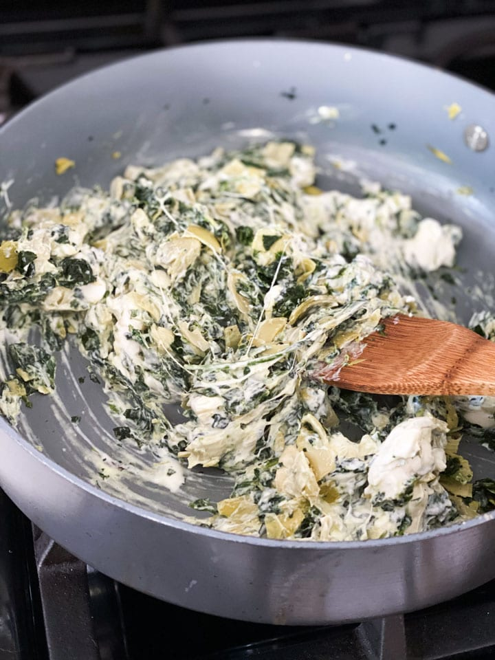 Mixing cheese into the cooked spinach and artichokes in a large pan