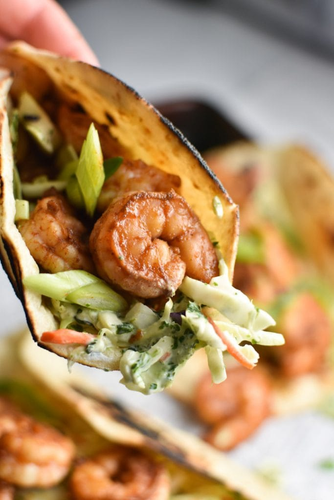 A close up shot of a spicy shrimp taco with creamy slaw coming out of the tortilla
