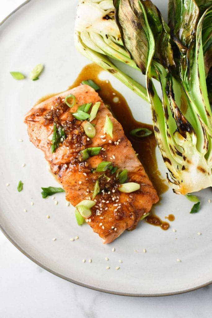 Salmon covered in a teriyaki sauce topped with green onion and sesame seeds