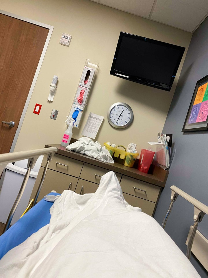 A woman lying in a hospital bed before an IVF embryo transfer
