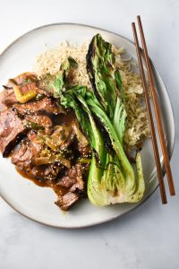 Gluten free mongolian beef with green onions on a plate with grilled bok choy and brown rice