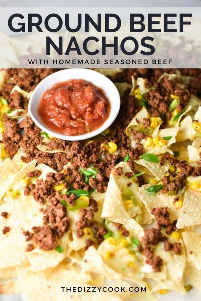A pile of ground beef nachos with salsa and green onions