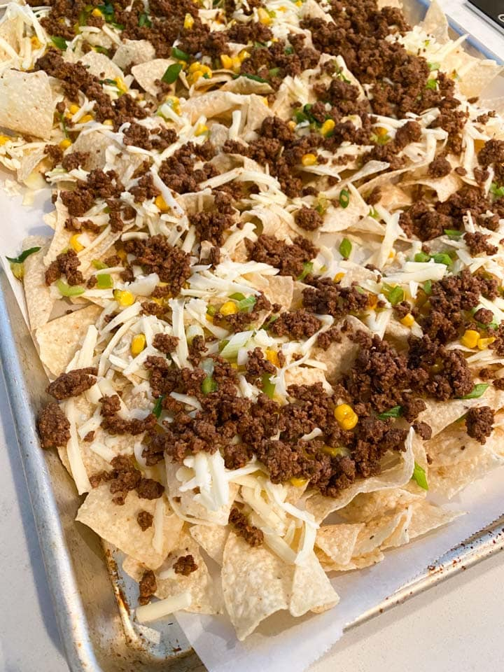 Nachos topped with ground beef and cheese before baking