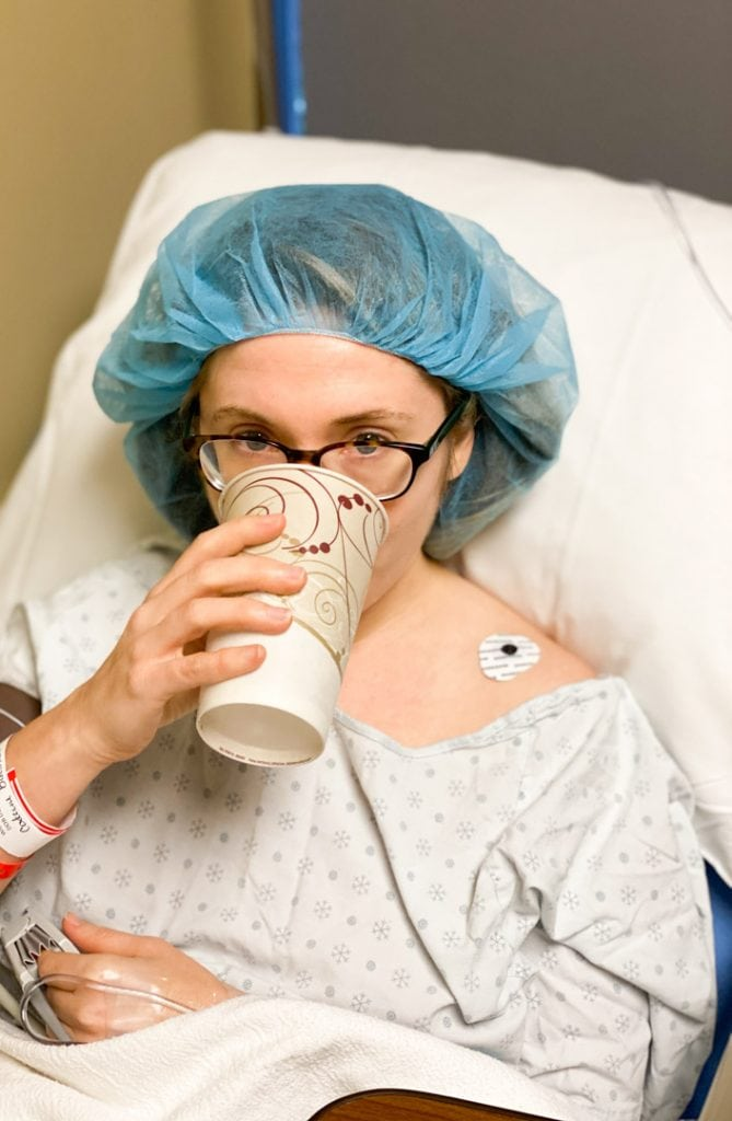 A woman drinking water after an IVF egg retrieval