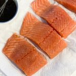 Raw salmon filets next to an Asian glaze sauce