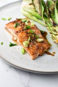 An Asian glazed salmon topped with sesame seeds on a plate with bok choy and green onion