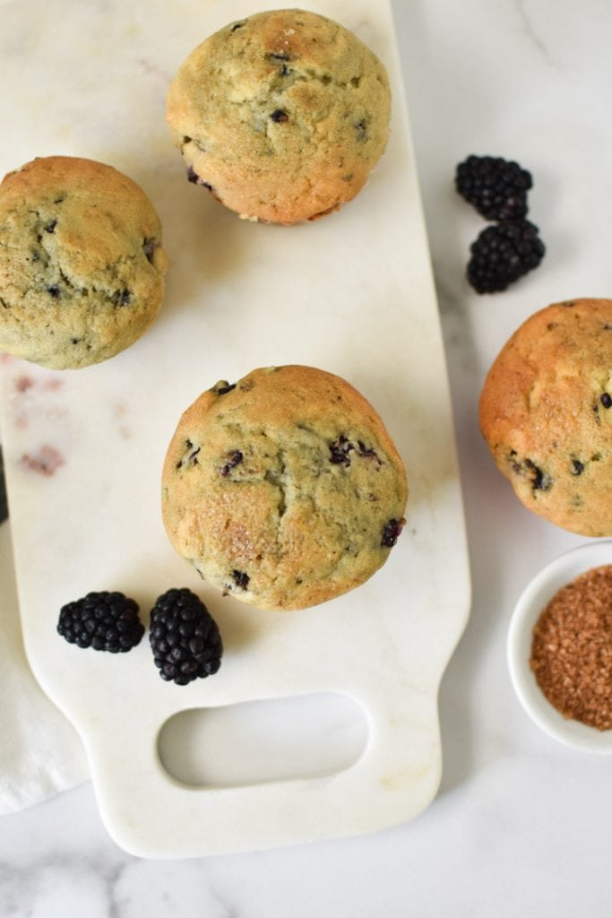 Blackberry muffins on a white marble table surrounded by fresh blackberries