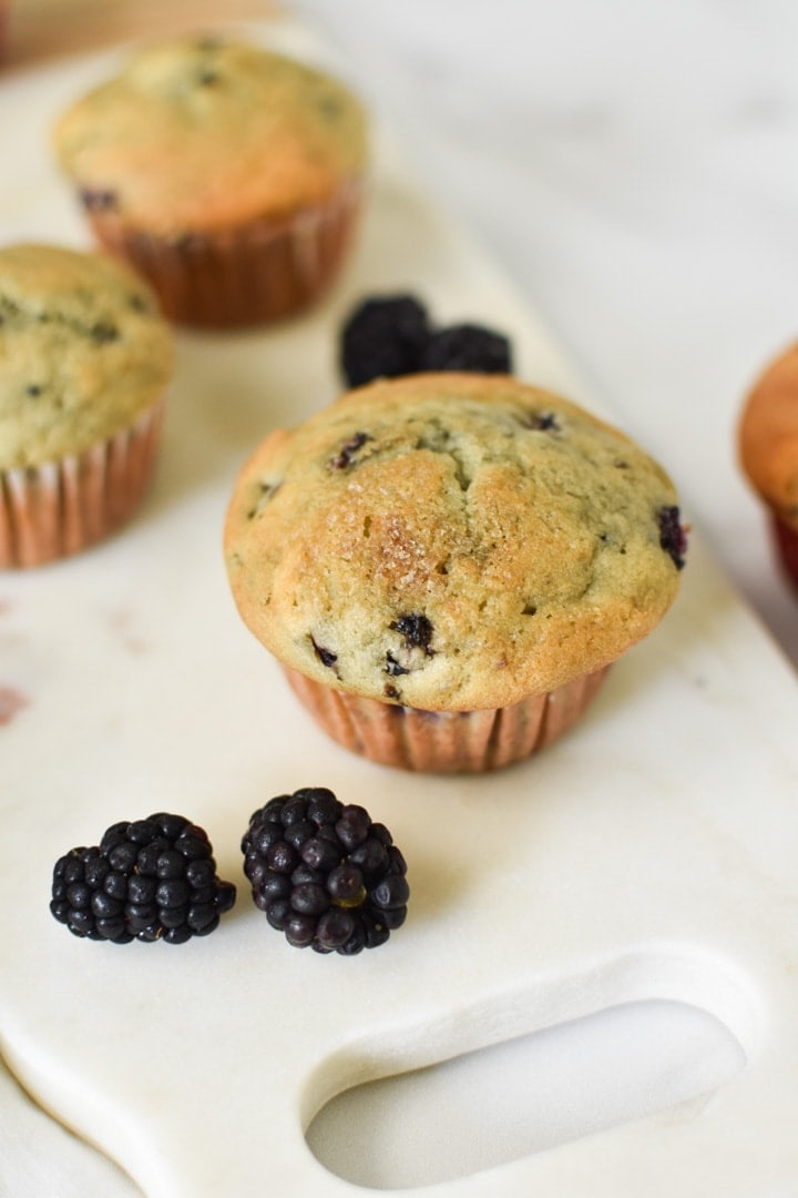 Blackberry cream cheese muffins on a marble serving dish
