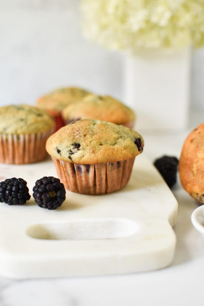 Blackberry muffins on a table with fresh berries and flowers