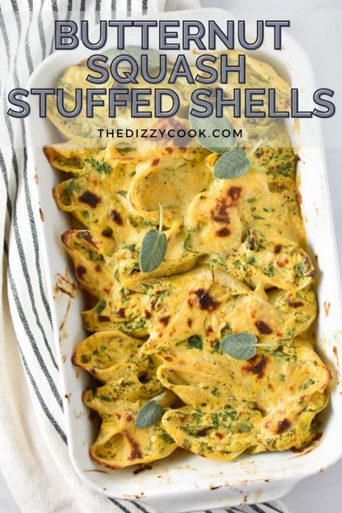 Baked butternut squash stuffed shells in a white baking dish next to a striped towel
