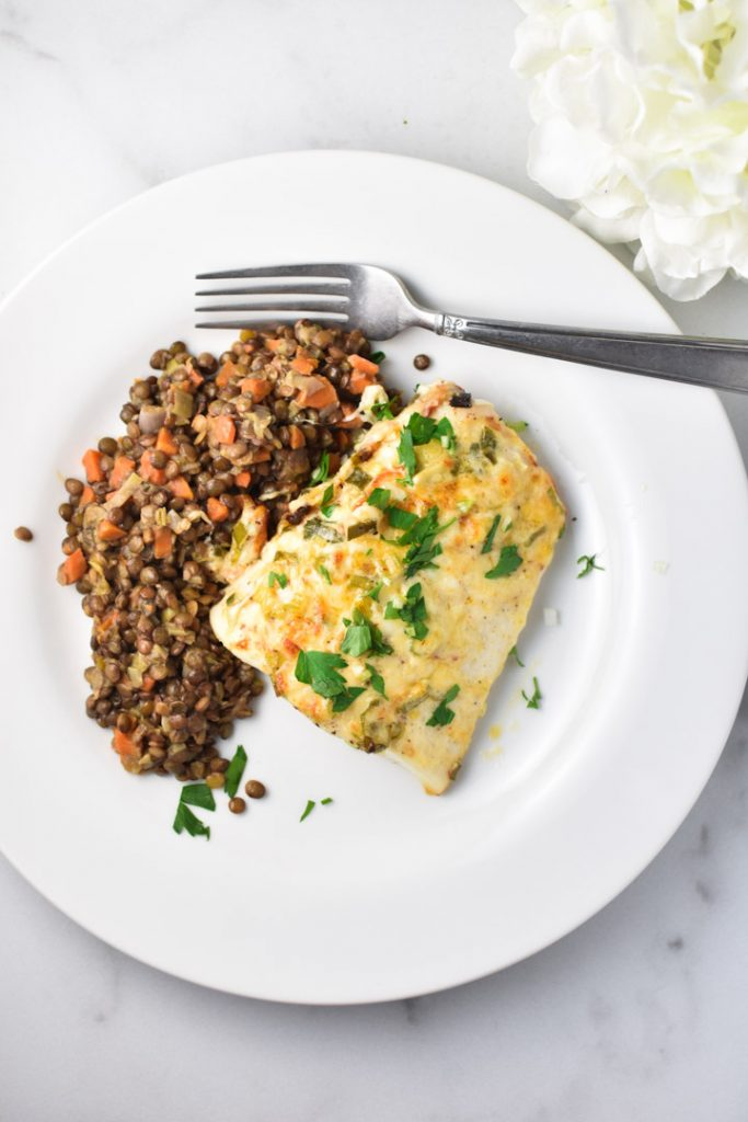 Heavenly halibut on a white plate with french lentils and a fork