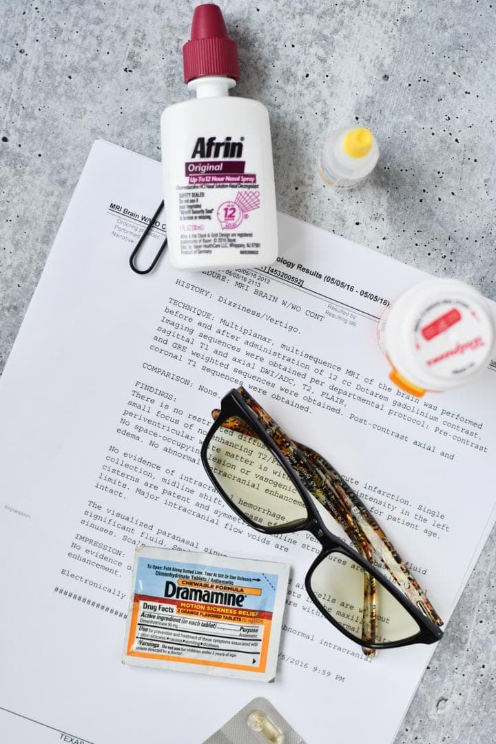 A bunch of vestibular migraine treatments like glasses and medication on a table with a diagnosis report