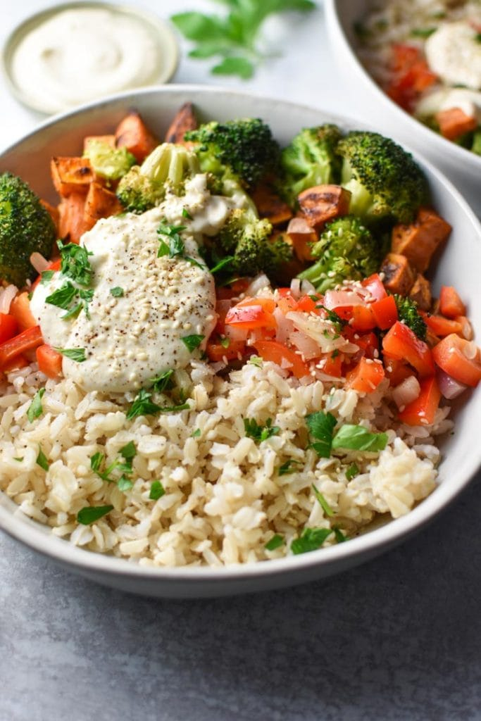 An up close photo of rice, peppers, and vegetables drizzled with a creamy tahini dressing