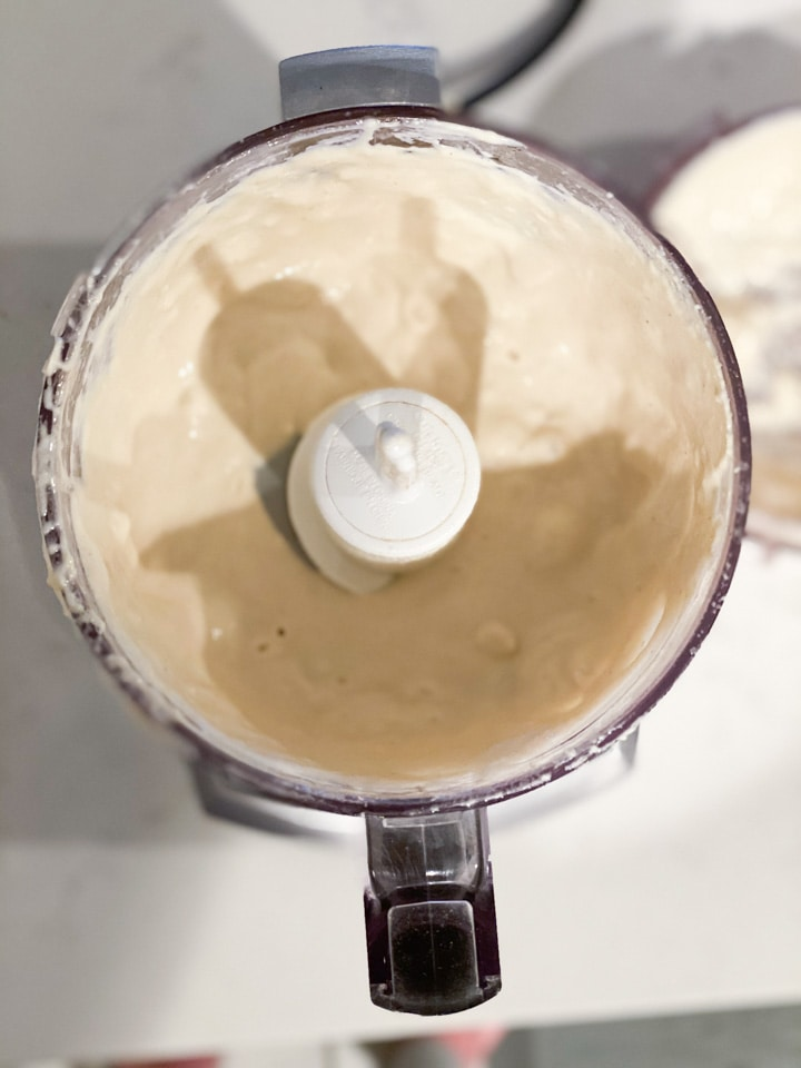 A small food processor with whipped creamy tahini dressing