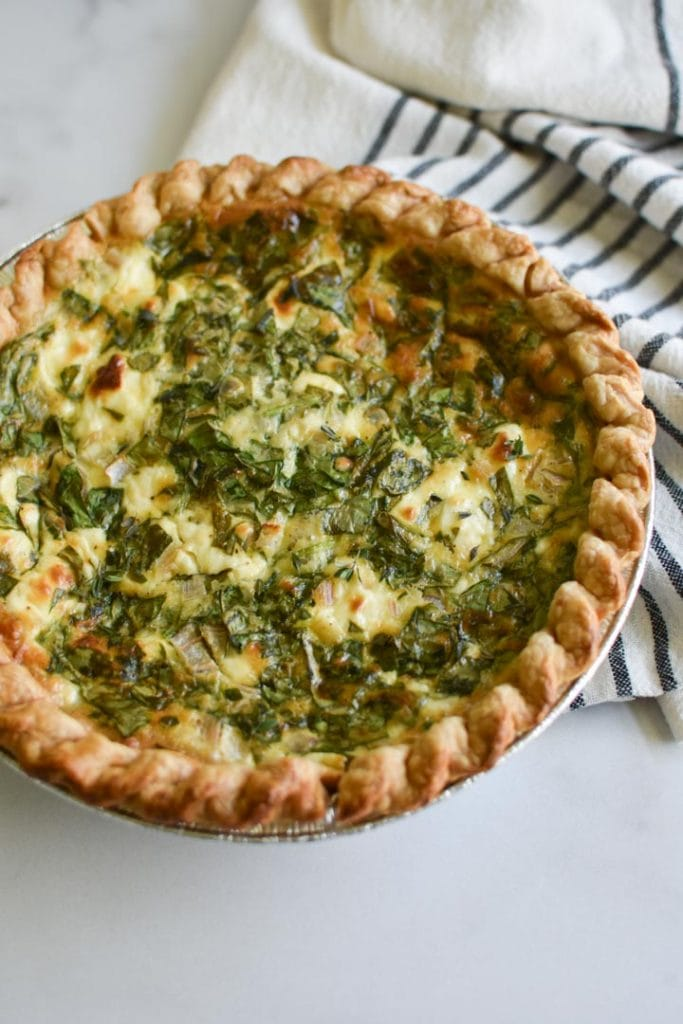 A spinach quiche on a striped towel