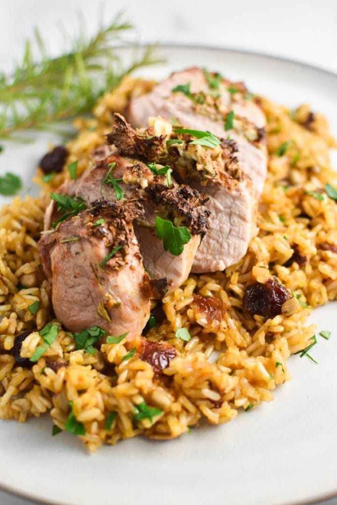 Sliced air fryer pork tenderloin served on wild rice with parsley