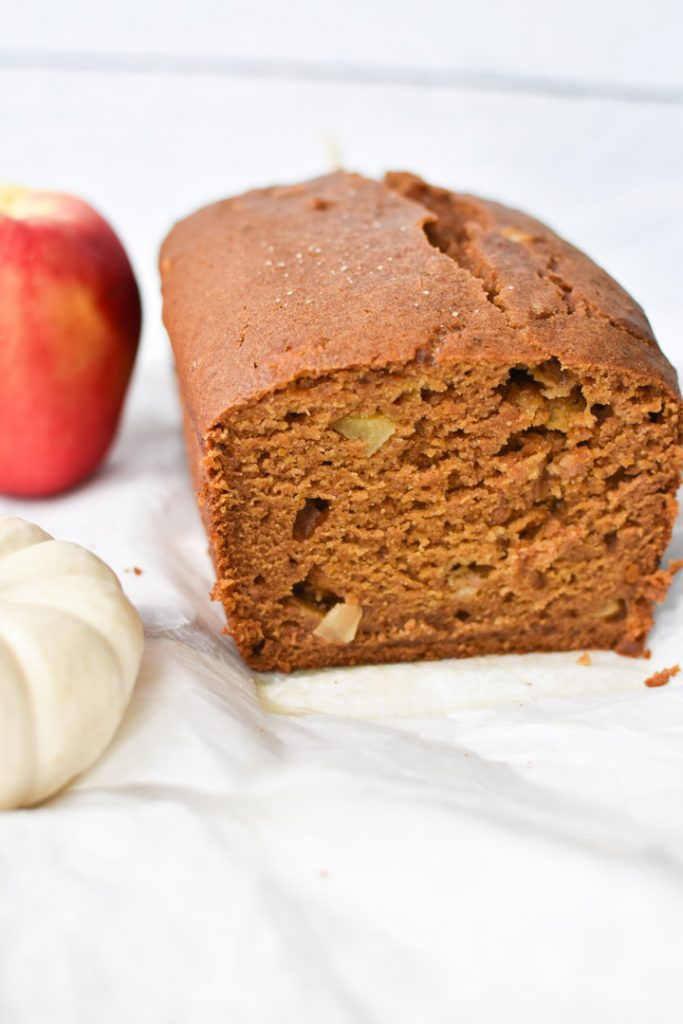 A baked pumpkin apple bread sliced so you can see the apples inside