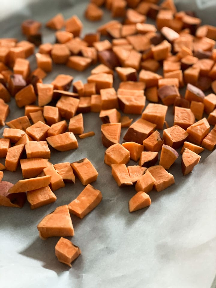 Chopped sweet potatoes on a roasting pan