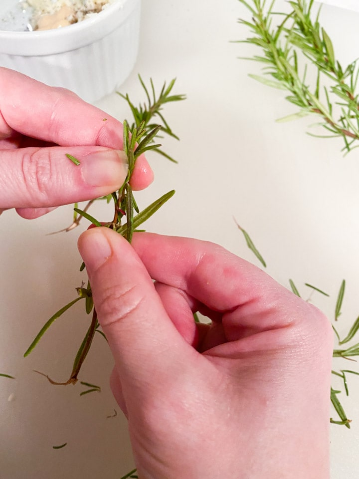 Two hands peeling the leaves off a rosemary stalk